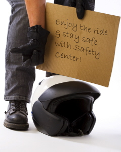 image of a person holding a sign with a motorcycle helmet sitting on the ground in front of him