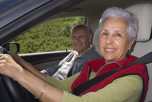 Two seniors in a car smiling