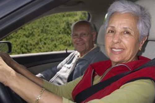 an image of an older senior couple driving in a car